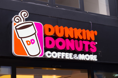 dunkin donuts sign in Essen, germany. Since its founding, the company has grown to become one of the largest coffee and baked goods chains in the world, with 11,000 restaurants in 33 different countries.