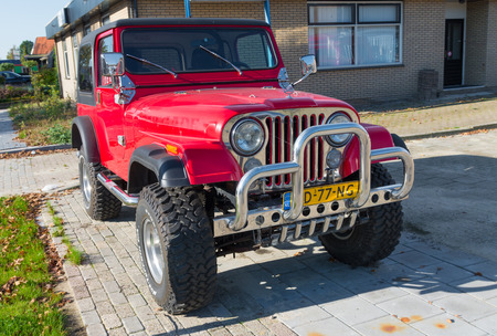 jeep: red jeep wrangler car with chrome bull bar. The production of the Wrangler began in 1987 and was succeeded in 1997 and 2007 by a second and a third generation, respectively.