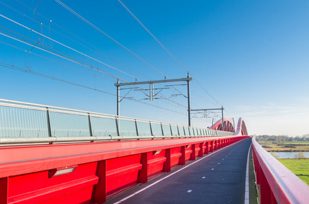 ijssel: bicycle lane along the new red railroad bridge over the IJssel river in the Netherlands Editorial