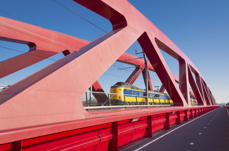 ijssel: train passing the new red railroad bridge over the IJssel river in the Netherlands