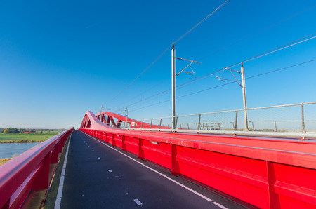 bicycle lane: bicycle lane along the new red railroad bridge over the IJssel river in the Netherlands Editorial