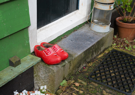 wooden shoes: pair of red wooden shoes in front of a doorstep