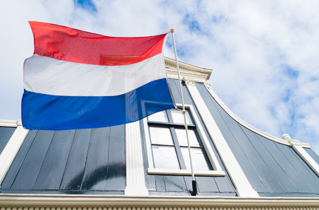 dutch flag: dutch flag in front of an authentic dutch house facade Stock Photo