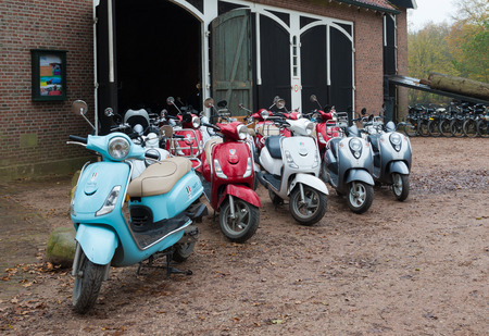 rented: DENEKAMP, NETHERLANDS - NOVEMBER 15, 2014: colorful italian scooters ready to be rented. Editorial