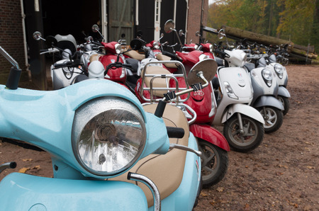rented: DENEKAMP, NETHERLANDS - NOVEMBER 15, 2014: colorful italian scooters ready to be rented. Stock Photo