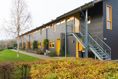 townhome: exterior of newly build townhomes with yellow doors and windows