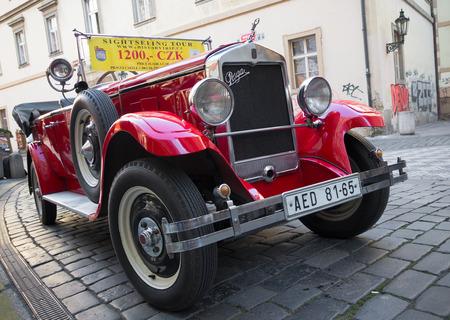 praga: PRAGUE - DECEMBER 23, 2014: Red Praga car used for sightseeing tours in the streets of prague. Editorial