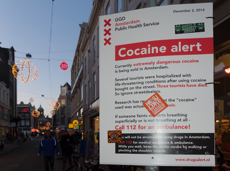 street drug: AMSTERDAM - JANUARY 4, 2015: Warning shield in the city center for dangerous, poisonous cocaine, also saying that several tourists have been killed using it. Editorial