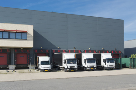 several trucks in front of a warehouse building Imagens