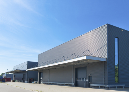 exterior of a modern warehouse building against a blue sky Stockfoto