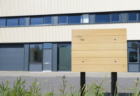 small office: blank wooden billboard in front of some small office units Stock Photo