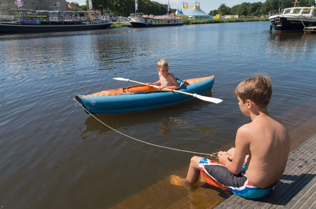 boys playing: OMMEN, NETHERLANDS - AUGUST 9, 2015: Two unknown boys playing with their canoe in the Regge river. The Regge area is a popular holiday region in the eastern netherlands