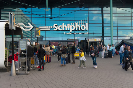 AMSTERDAM - AUGUST 28, 2015: Unknown travelers at the main entrance of amsterdam schiphol airport