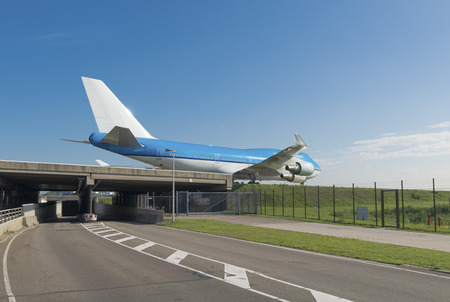passenger airplane over a highway taxiing to the runway