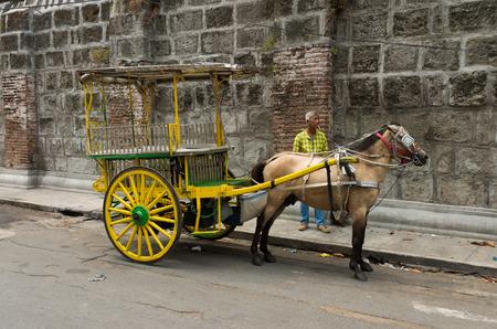 horse drawn carriage: MANILA, PHILIPPINES - JUNE 7, 2015: Unknown man with horse drawn carriage in Intramuros, the monumental spanish part of Manila