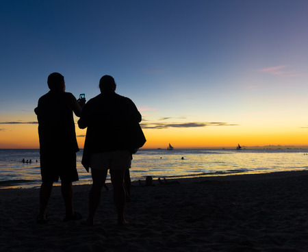 pics: elderly couple taking pics from a beautiful sunset on a tropical beach Stock Photo