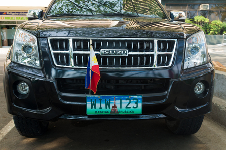 license plate: MANILA, PHILIPPINES - JUNE 7, 2015: Isuzu car with philippine flag and license plate. 2.5 million cars in Manila cause 85% of the air pollution.