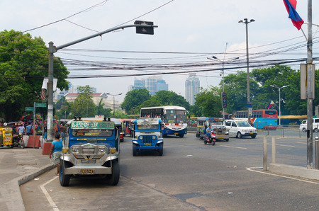 public transportation: MANILA, PHILIPPINES - JUNE 7, 2015: Jeepneys in the streets of Manila. Jeepneys are the most popular means of public transportation in the Philippines. Editorial