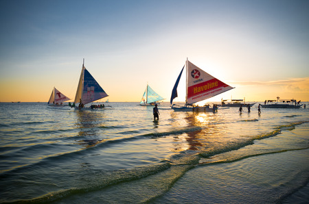 boracay: BORACAY, PHILIPPINES - MAY 17, 2015: Traditional philippine sailing boats just before sunset on boracay island, the most touristic destination of the philippines Editorial
