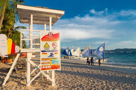 boracay: BORACAY, PHILIPPINES - MAY 20, 2015: white life guard tower with safwety instructions on the beautiful white beach of boracay, the main tourist attraction in the philippines Stock Photo