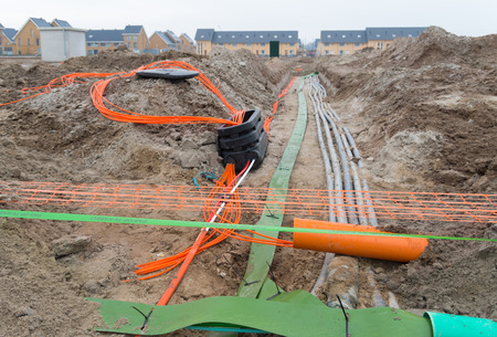 orange and green cables in the ground. The text on the green band says: watch out television cable Stock Photo