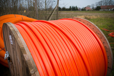 fiberoptic: HENGELO, NETHERLANDS - MARCH 28, 2015: Drums with orange fiber cable owned by Reggefiber, a Dutch company that specializes in the installation of fiber optic connections Editorial