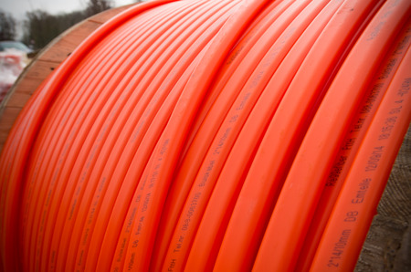 fiberoptic: HENGELO, NETHERLANDS - MARCH 28, 2015: Orange fiber cable owned by Reggefiber, a Dutch company that specializes in the installation of fiber optic connections