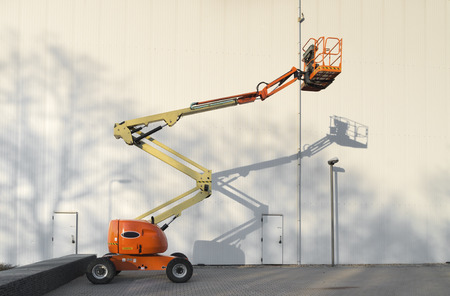 reach truck: little mobile hydraulic crane making a shadow against the wall Stock Photo