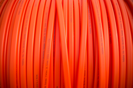 fiberoptic: HENGELO, NETHERLANDS - MARCH 28, 2015: Closeup of orange fiber cable owned by Reggefiber, a Dutch company that specializes in the installation of fiber optic connections Editorial