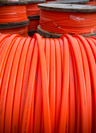 specializes: HENGELO, NETHERLANDS - MARCH 28, 2015: Drums with orange fiber cable owned by Reggefiber, a Dutch company that specializes in the installation of fiber optic connections Editorial