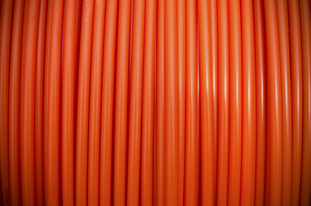 fiberoptic: background of a roll of orange fiber cable Stock Photo