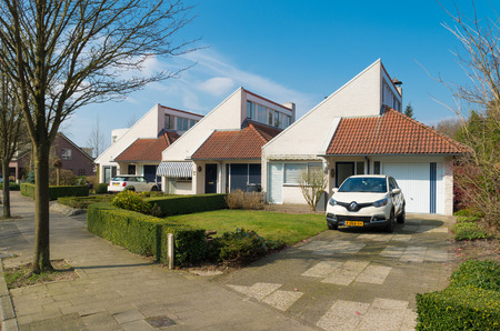 detached houses: OLDENZAAL, NETHERLANDS - MARCH 23, 2015: Modern row of identical detached houses with front garden and own parking lot