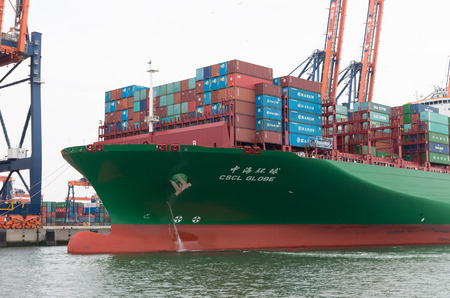 maneuvering: ROTTERDAM, NETHERLANDS - JUNE 28, 2015: CSCL Globe container ship mooring in the Rotterdam harbor. The CSCL Globe measures 400 meters in length, 58.6 meters in width and 30.5 meters in depth.