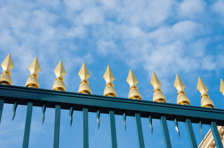 green metal gate with decorative golden spikes
