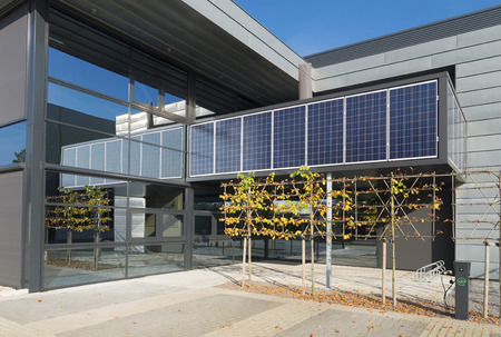 modern office building exterior with solar panels above the entrance