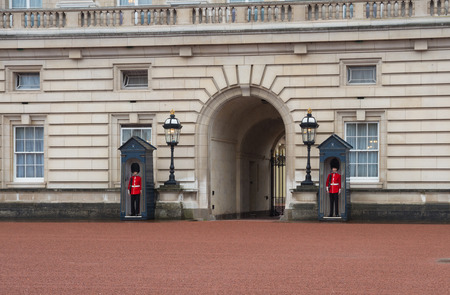 reigning: LONDON, ENGLAND - OCTOBER 21: British Royal Guards at the entrance of Buckingham palace. Buckingham Palace is the London residence and administrative headquarters of the reigning monarch of the United Kingdom