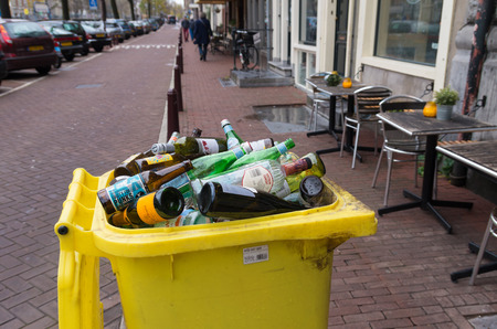 managing waste: AMSTERDAM, NETHERLANDS - NOVEMBER 15, 2015: Yellow bin filled with empty bottles in the streets of amsterdam