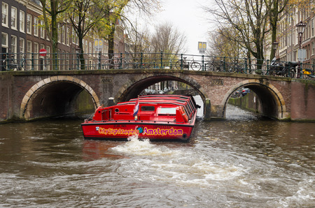 gabled houses: AMSTERDAM, NETHERLANDS - NOVEMBER 15, 2015: Red sightseeing boat sailing through the amsterdam canals. The city counts 165 canals.