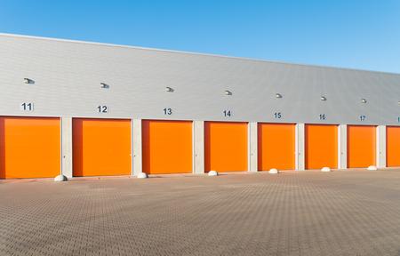 buitenkant van een commerciële magazijn met oranje roldeuren