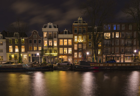 night view of some traditional gabled houses along an amsterdam canal