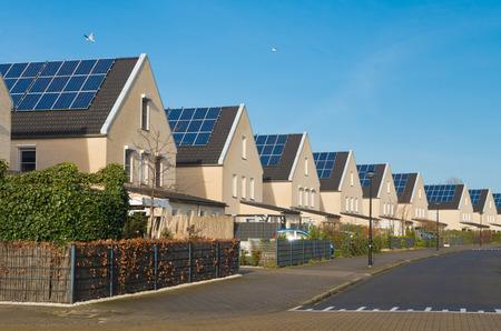 rij van nieuw te bouwen moderne huizen met zonnepanelen in Nederland