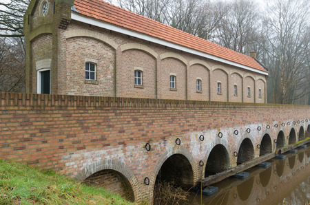 dutch canal house: restored sluice house or Schuivenhuisje in dutch language along the hand-dug almelo nordhorn canal in the netherlands
