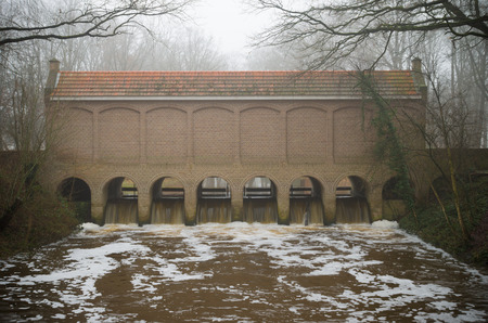 canal house: restored sluice house or Schuivenhuisje in dutch language along the hand-dug almelo nordhorn canal in the netherlands