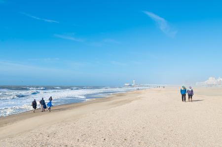 Few people braving the fierce wind on the north sea beach with the scheveningen pier in the background Editorial