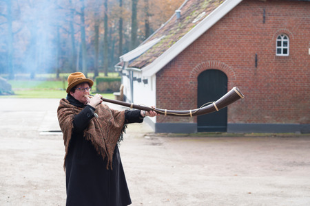 alphorn: OLDENZAAL, NETHERLANDS - NOVEMBER 27, 2016: Unknown woman blowing a so called midwinterhorn, a traditional handmade wooden instument. It is used in the advent period in some eastern parts of the netherlands Editorial