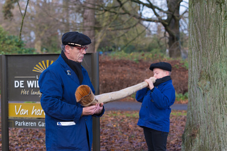 alphorn: OLDENZAAL, NETHERLANDS - NOVEMBER 27, 2016: Unknown young boy blowing a so called midwinterhorn, a traditional handmade wooden instument. It is used in the advent period in some eastern parts of the netherlands