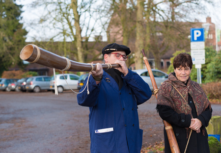 alphorn: OLDENZAAL, NETHERLANDS - NOVEMBER 27, 2016: Unknown man blowing a so called midwinterhorn, a traditional handmade wooden instument. It is used in the advent period in some eastern parts of the netherlands