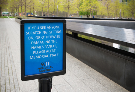 keep an eye on: NEW YORK - APRIL 27, 2016: Information shield at the 911 memorial with a warning to keep an eye on people who damage the names panels Editorial