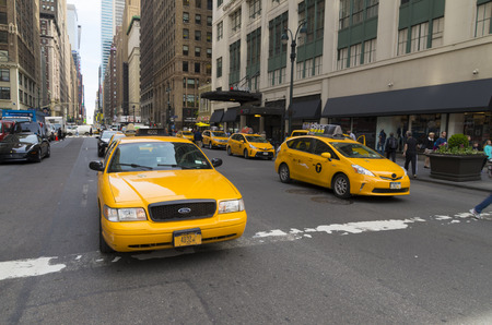 taxicabs: NEW YORK - APRIL 28, 2016: Typically yellow medallion taxicabs in front of Macys department store. They are widely recognized icons of the city and come in two varieties: yellow and green.