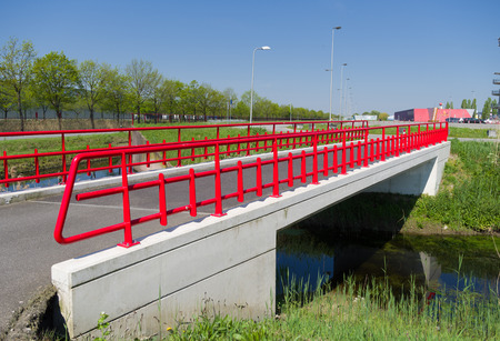 small pedestrian bridge with a red metal railing